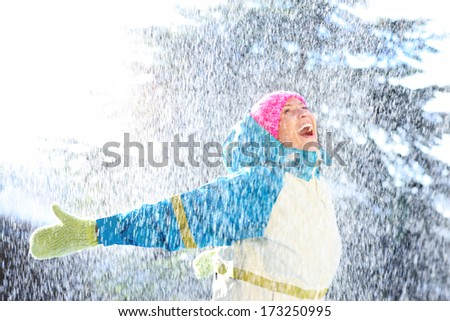 A picture of a joyful woman playing in the snow - stock photo