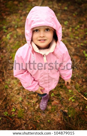 A picture of a little girl in pink outfit walking in the forest - stock photo