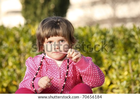A picture of a little girl sitting in the park and trying to use a lip gloss