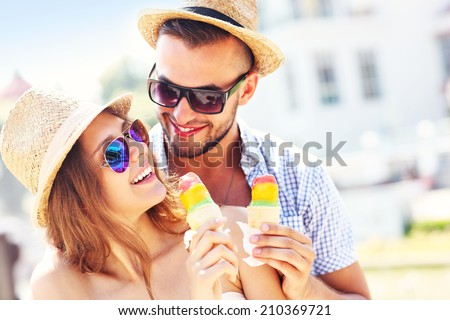 A picture of a lovely couple eating ice-cream in the city - stock photo
