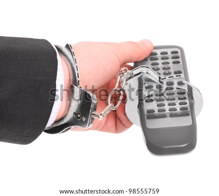 A picture of a male hand chained to remote control over white background