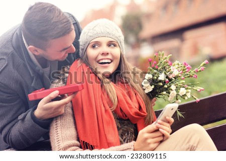 A picture of a man giving surprise gift to woman in the park