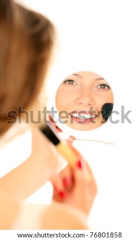 A picture of a mirror reflection of a beautiful girl putting on make-up