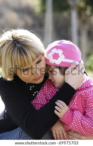 A picture of a mum comforting and hugging her baby girl in the park - stock photo