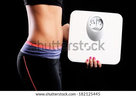 A picture of a muscular female belly and a white bathroom scales over black background