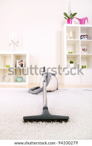A picture of a new vacuum cleaner standing in the living room - stock photo