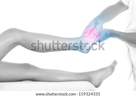 A picture of a physio therapist giving a foot massage over white background - stock photo