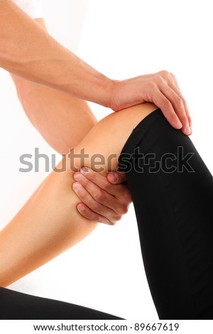 A picture of a physio therapist trying to fix the leg over white background - stock photo