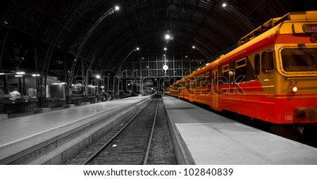 A picture of a railwaystation with a red train in it. With the rest of the picture beeing black and white.