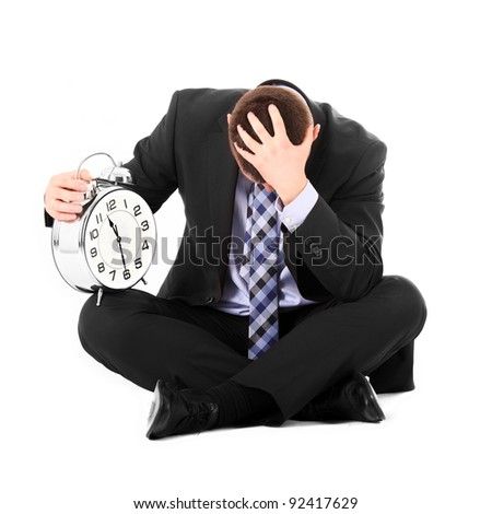 A picture of a sad businessman sitting over white background with a clock - stock photo