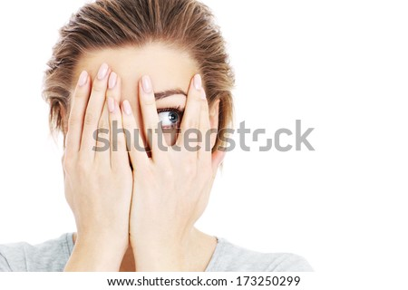 A picture of a scared woman covering her eyes over white background - stock photo