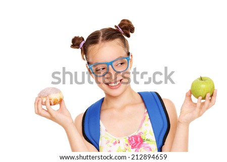 A picture of a schoolgirl with healthy and unhealthy lunch to choose from - stock photo