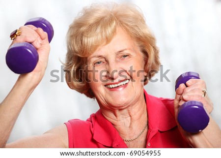 A picture of a senior lady working out with weights over white background - stock photo