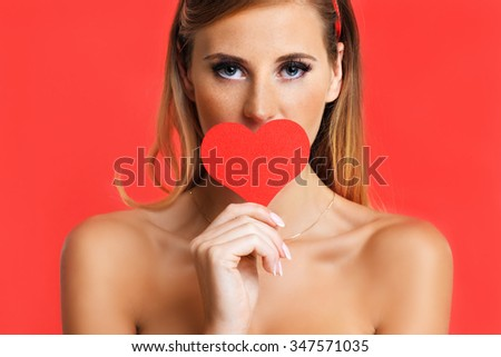 A picture of a sexy Valentine woman holding a heart over red background