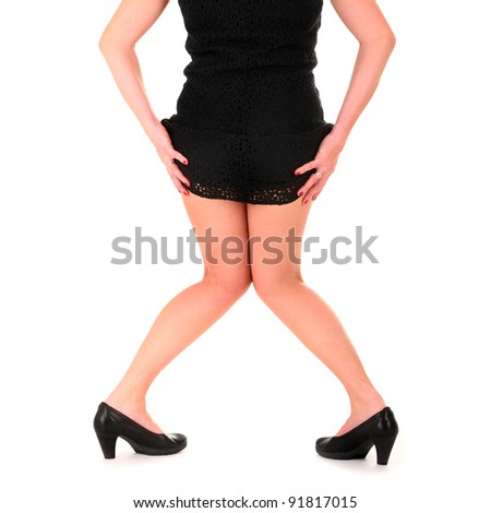 A picture of a sexy woman in a black dress and heels over white background - stock photo