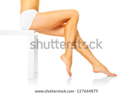 A picture of a sexy woman sitting over white background and showing her legs - stock photo