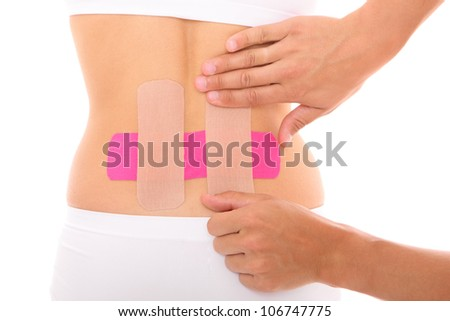 A picture of a special physio tape being put on the back muscle over white background - stock photo