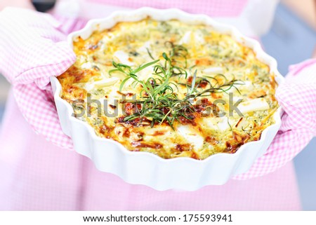 A picture of a spinach quiche hold in oven gloves over pink apron - stock photo