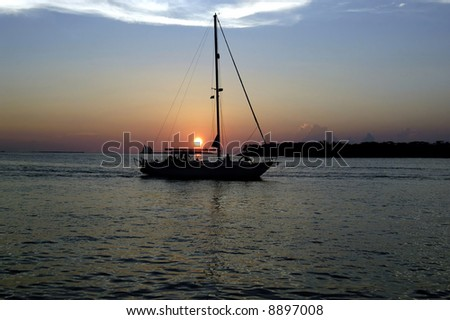A picture of a sunset at key west with a sail boat as a silhouette - stock photo