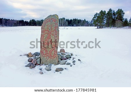 A picture of a swedish runestone standing in a winter landscape field, showing woods in the background. - stock photo