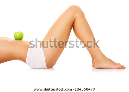 A picture of a woman holding a green apple on her fit belly - stock photo