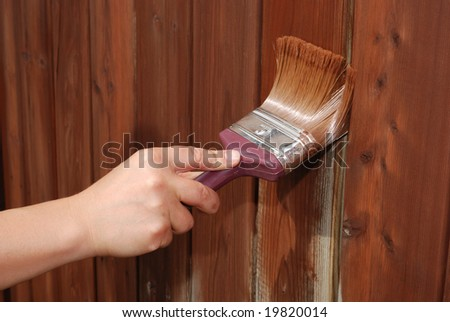 A picture of a woman painting fence - stock photo