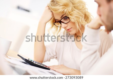 A picture of a worried couple with documents at home - stock photo