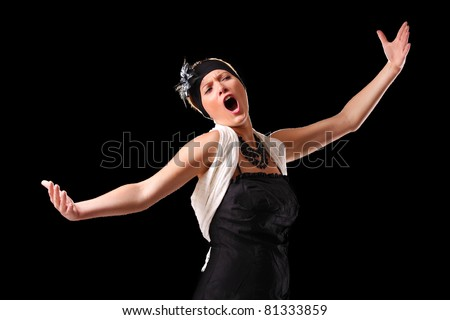 A picture of a young beautiful opera singer performing over black background - stock photo