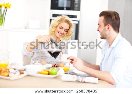 A picture of a young couple eating breakfast in the kitchen