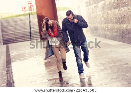 A picture of a young couple running in the rain in the city - stock photo