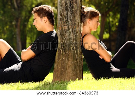 A picture of a young couple sitting in the park and being in a conflict - stock photo