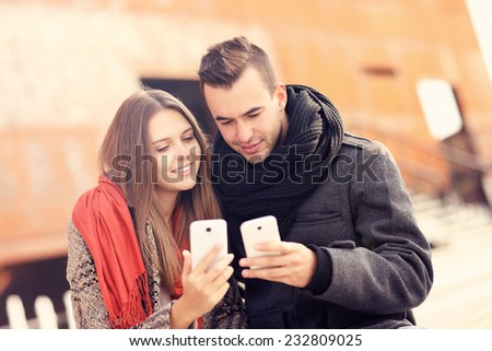 A picture of a young couple sitting on a bench and using smartphones on an autumn day - stock photo