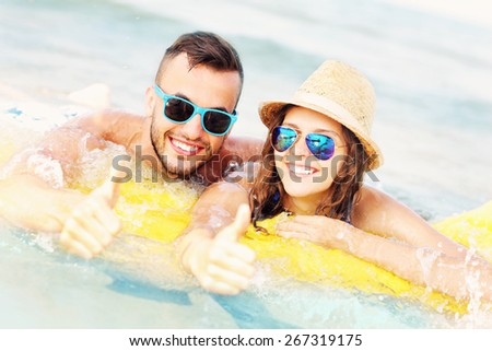 A picture of a young couple swimming on a matress in the sea - stock photo