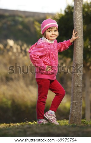 A picture of a young cute girl posing by the tree in the park - stock photo