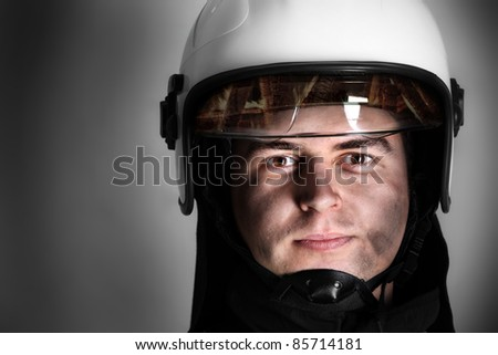A picture of a young firefighter in a white helmet looking against grey background