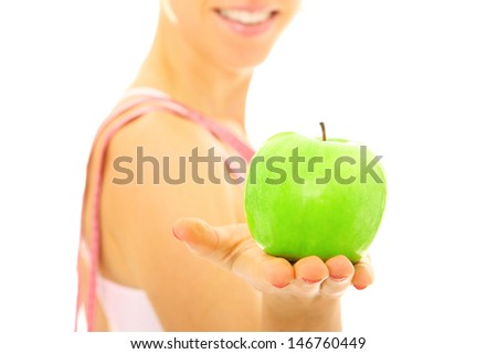 A picture of a young fit woman showing a green apple over white background