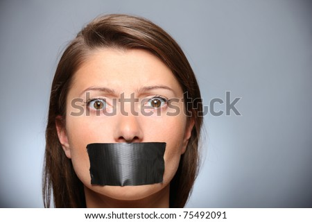 A picture of a young girl with her lips covered by a tape over grey background - stock photo