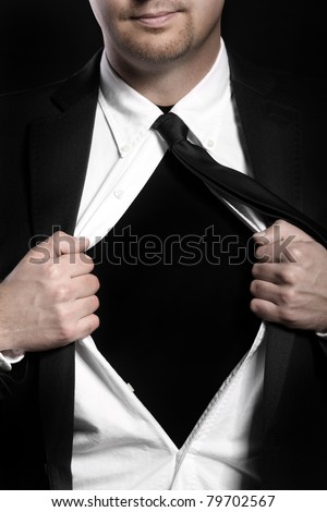 A picture of a young handsome man tearing off his shirt over black background - stock photo