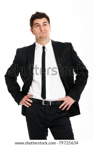 A picture of a young handsome undecided businessman standing over white background