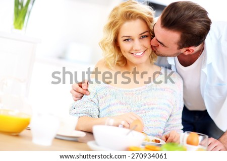 A picture of a young man giving a good morning kiss to his wife in the kitchen - stock photo