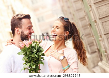 A picture of a young romantic couple with flowers in the city - stock photo