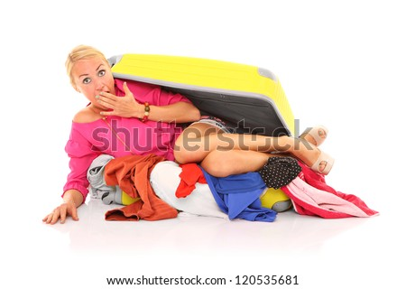 A picture of a young sexy woman trying to pack herself into the suitcase over white background - stock photo
