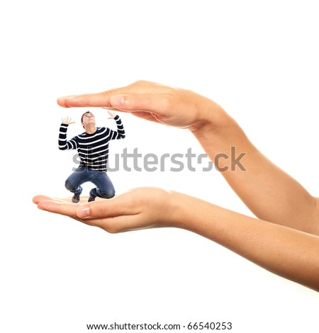 A picture of a young stressed man trapped in big hands over white background - stock photo