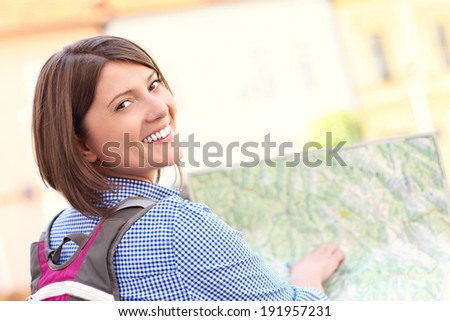 A picture of a young tourist with a map in a town - stock photo