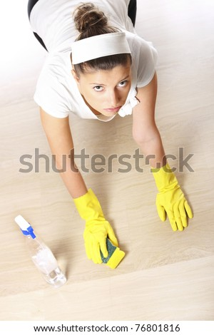 A picture of a young woman cleaning the floor over light background - stock photo