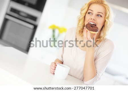 A picture of a young woman eating donut with morning coffee