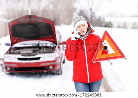 A picture of a young woman having a problem with a car on a winter road - stock photo