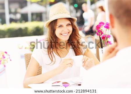 A picture of a young woman sitting in the cafe during summer day - stock photo