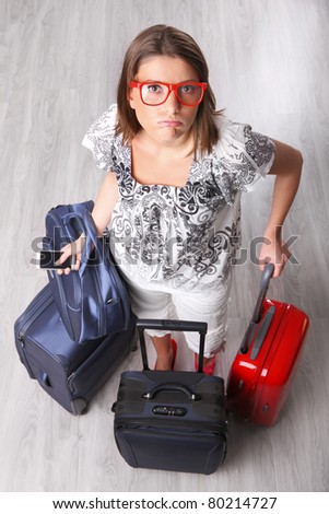 A picture of a young woman waiting with many pieces of luggage at the airport - stock photo