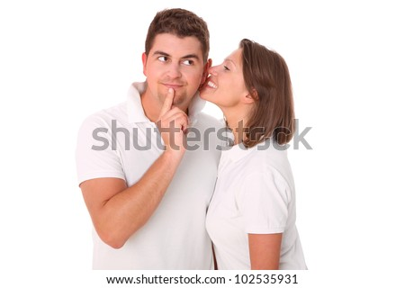 A picture of a young woman whispering to her boyfriend over white background - stock photo